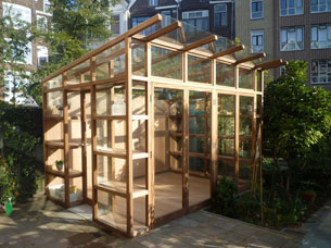 A conservatory in iroko and glass, in the garden of a house in Rotterdam.