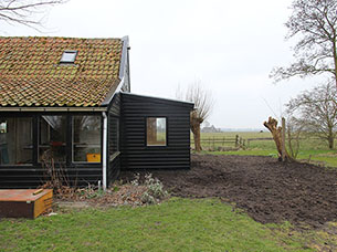 Extension for a wooden house in the polder of Noord-Holland, next to the dyke of the IJsselmeer.
